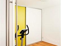 Posuvné dveře oddělují obývací pokoj  od části určené k relaxaci a cvičení. Jsou tu vestavěné skříně ve stejných barvách jako v obývacím pokoji.