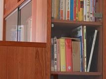 Oddělující skříňka v ložnici má ze strany postele malou knihovnu