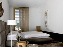 K ložnici přiléhá šatna i koupelna. Místnosti vévodí postel značky Poliform a posezení nabízí židle Wiggle Side Chair od
