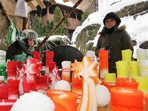 Stánek se svíčkami na nádvoří hradu Loket při vánočních trzích.