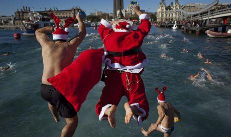 Atleti převlečení za Santa Clause skáčou do moře při akci Copa Nadal v Barceloně (24. prosince 2010)