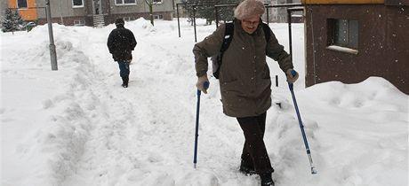 Na sídlišti Dobiášova v Liberci chodí lidé místo po chodníku hlubokým sněhem.
