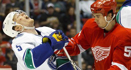 Vancouversk� obr�nce Christian Ehrhoff (vlevo) inkasuje �der v souboji  s Jonathanem Ericssonem z Detroitu.