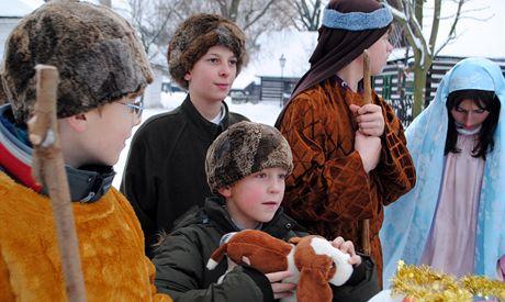 Děti z Centra Jana XXIII. pózují ve skanzenu lidových staveb Betlém v Hlinsku. Vytvořily živý betlém.