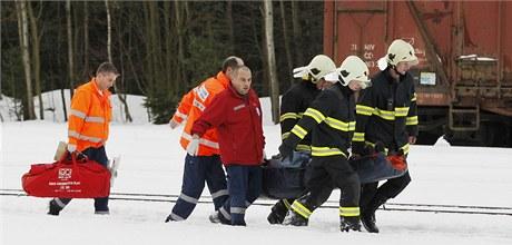 Záchranáři odnášejí zraněného cestujícího k vrtulníku.