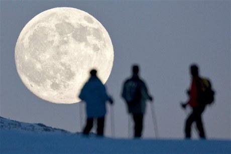 Švýcarští lyžaři hledí směrem k Měsíci v úplňku. (21. prosince 2010)
