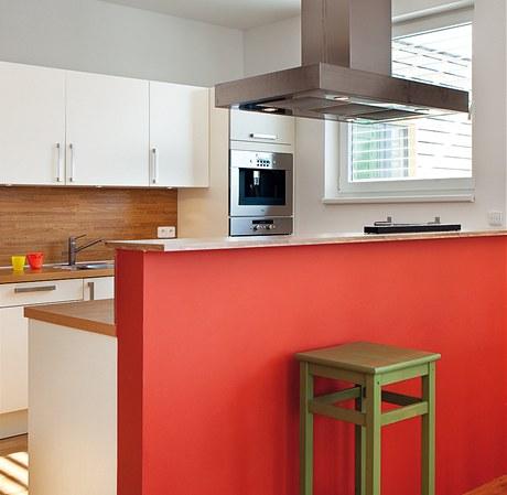 Cihlová barva ze stěny se opakuje i na kuchyňském předělu