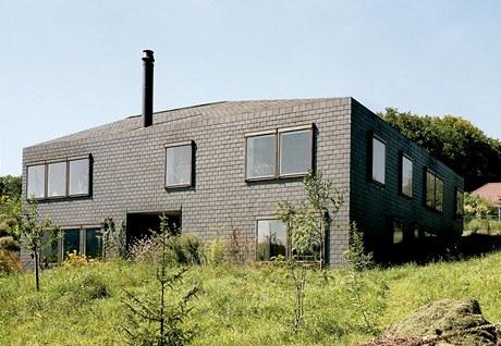 Pohled jižní. Díky kompaktnímu tvaru budova harmonicky zapadá do krajiny. Velké zapuštěné zádveří uprostřed jižního průčelí