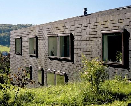 Fasády mají opačnou plasticitu, než je u rodinného domu obvyklé – okna nejsou zapuštěná, ale předsazená před obvodovou plochu. Ve střešních plochách i svislých stěnách jsou totiž použita střešní okna.