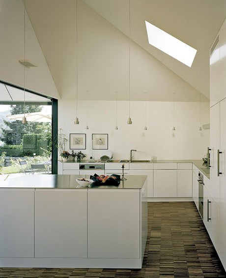 Kuchyňská linka s bíle lakovanými dvířky bez úchytek a skleněnou pracovní deskou zapadá do celkového minimalistického konceptu