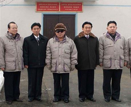 Kim Čong-il uprostřed na obhlídce továrny se svým nejmladším synem a nástupcem Kim Čong-unem (zcela vpravo)
