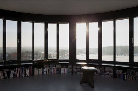 Dokonalému výhledu z obývacího pokoje v nejvyšším patře je uzpůsobena i knihovna, která respektuje linii oken