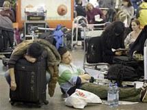 Vyčerpaní cestující čekají na své spoje na Šeremeťjevě letišti v Rusku
