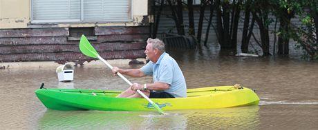 Christopher Roth pádluje zaplavenou ulicí ve městě Bundaberg v Queenslandu (29. prosince 2010)