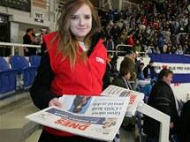 Hosteska rozdává na zápase Kometa v. Kladno noviny MF DNES. (7. leden 2011)