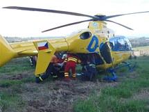 Hasiči nakládají do vrtulníku muže, pod kterým se na Opavsku propadla lávka.