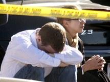 Zhroucení obyvatelé Tusconu posedávají na místě, kde střelec spustil palbu (8. ledna 2010)