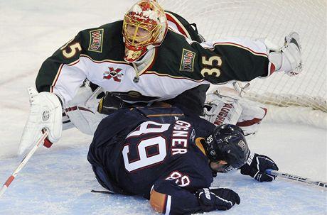 Brank�ø Anton Chudobin z Minnesoty pøepad�v� pøes edmontonsk�ho �toèn�ka Sama Gagnera v jednom z �tern�ch z�pasù NHL.