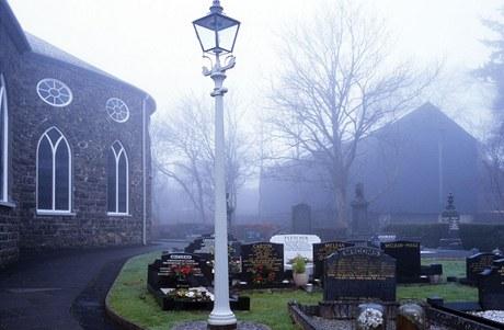 Blízký hřbitov a kostel výrazně ovlivnily vzhled stavby