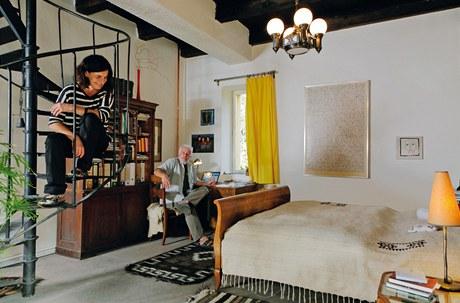 Části obytného prostoru spojuje tmavý trámový strop a světlý koberec