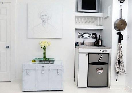 Součástí malého pokojíku je i miniaturní kuchyňka