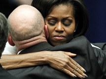 Michelle Obamová objímá manžela postřelené kongresmanky při smutečním ceremoniálu v arizonském Tucsonu (12. ledna 2011)