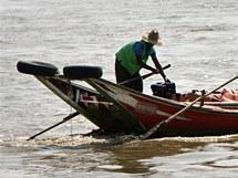 Na rangúnské řece se malé rybářské bárky proplétají s nákladními loděmi