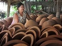 Barmánka kontroluje, zda je vyrobená keramika v pořádku