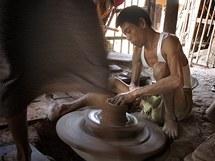 Muž tvaruje nádobu a manželka mu nohou roztáčí hrnčířský kruh