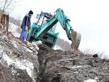 Vodu ze silnice do Bošířan se snaží odvést do strouhy, kterou vykopal bagr.