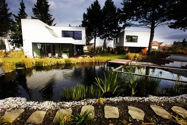 Dva rodinné domy jsou vsunuté mezi vzrostlé stromy, p�írodní charakter dopl�uje koupací jezírko kombinované s bazénem