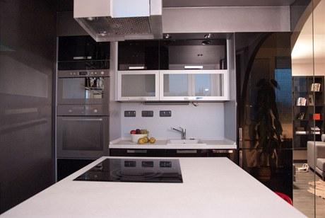 Černá kuchyně v lesku má netradičně umístěnou varnou plochu