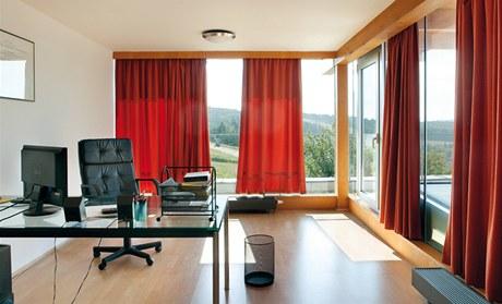 Okna v pracovně jsou zastíněna závěsy, původní návrh však počítal s předokenními žaluziemi