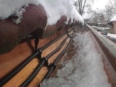 Kvůli ledu v okapech může voda z tajícího sněhu zatéct do podkroví