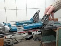 Do vázání se upnou přípravky nahrazující botu. Umožňují při servisu uchopit lyže za vázání