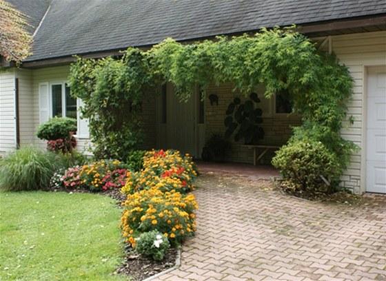 Vstup do domu tvoří otevřené venkovní zádveří, lemované bujnou zelení