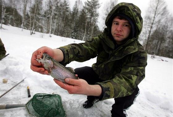 Rybář Michal Šanta ukazuje uloveného pstruha.