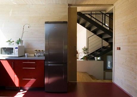 Kuchyně je od obývacího prostoru oddělena posuvnými dveřmi. Podlahu pokrývá marmoleum, linka je vyrobena z lakovaných MDFdesek s vysokým leskem. Zdroj: www.mujdum.cz