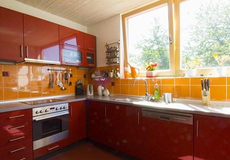 Zatímco v ostatních částech domu převažuje struktura přírodního dřeva, zde architekt použil hladké plochy a výraznou červenou barvu. Zdroj: www.mujdum.cz