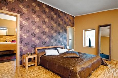 Ložnice rodičů sousedí s koupelnou i prostornou šatnou. Nepřehlédnutelná je tapeta Rasch, dřevěný nábytek majitelé objevili na internetu, textil a zrcadlo v masivním rámu jsou z Ikea