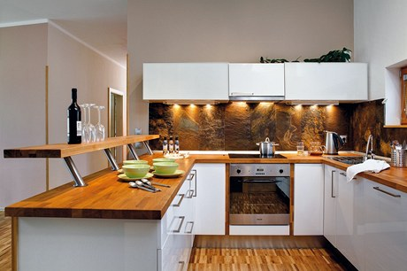 """Kuchyňskou linku umístěnou do """"U"""" s povrchem skříněk ve vysokém lesku a s dřevěnou pracovní deskou si manželé vybrali v Ikea. Filip se postaral o obložení stěn nad pracovní deskou přírodní břidlicí"""