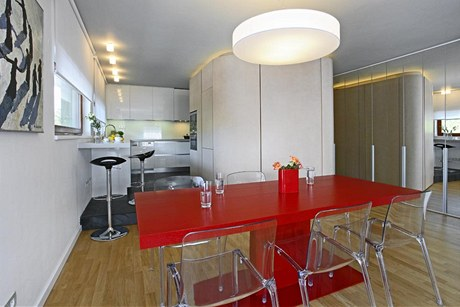 Barevně neutrální interiér oživuje červený stůl