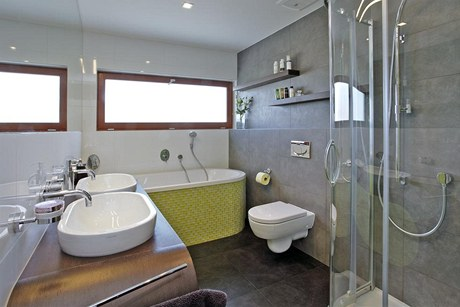 Barevnost koupelnového nábytku je sladěna s odstínem mozaiky. Prostor tak působí uceleným dojmem.