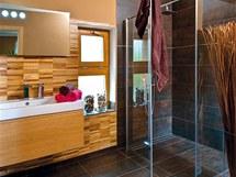 Dřevěnou mozaiku, jež slouží i jako obklad, doplňuje velkoformátová dlažba