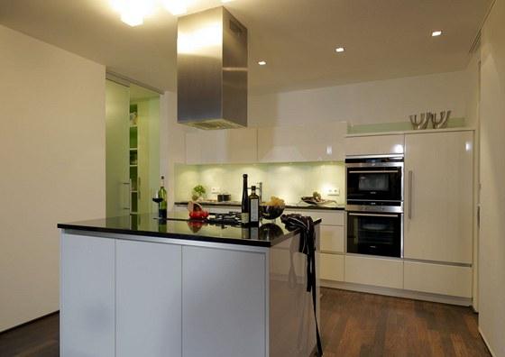 Typická současná kuchyně: ostrůvek, bílý lak, téměř bezúchytkové řešení