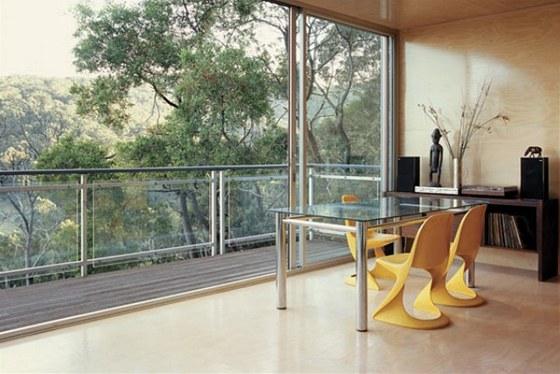 Interiéru obývacího pokoje s kuchyní vévodí dřevo a pohled ven do přírody