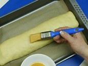 Závin přeložte na plech s pečicím papírem a potřete ho rozšlehaným vejcem