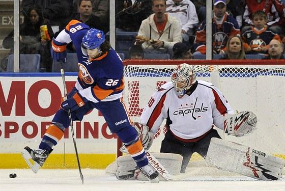 Matt Moulson z New Yorku Islanders se sna�� te�ovat puk p�ed brank��em Washingtonu Michalem Neuvirthem.