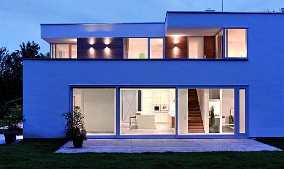 Bílá barva a dřevo se opakují jak v exteriéru domu, tak v interiéru