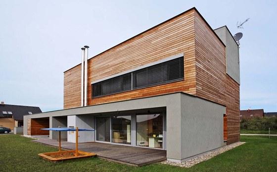 Prosklené přízemí přechází na jižní straně domu v dřevěnou terasu s venkovním krbem. Přesahující střecha a boční stěny vytvářejí intimní pocit. Zdroj: www.mujdum.cz